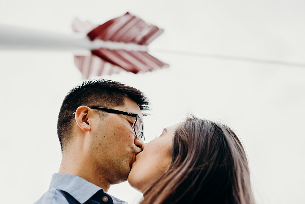Engaged couple kisses with the arrow from Cupid's Span in the background.