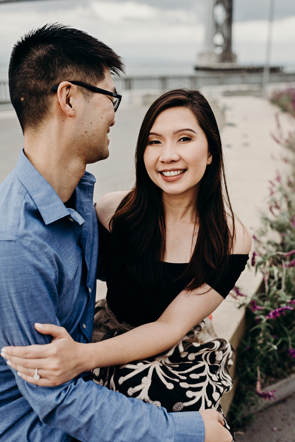 Woman smiles at the camera as her fiancé smiles at her in front of the San Francisco–Oakland Bay Bridge.