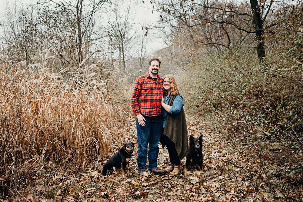 Engaged couple stands with their dogs on a path of fallen leaves.