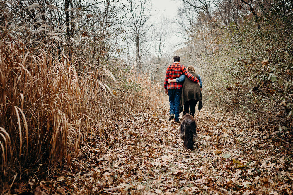 Engaged couple walks with arms around each other down a path in the fall woods with their dog trailing behind them.