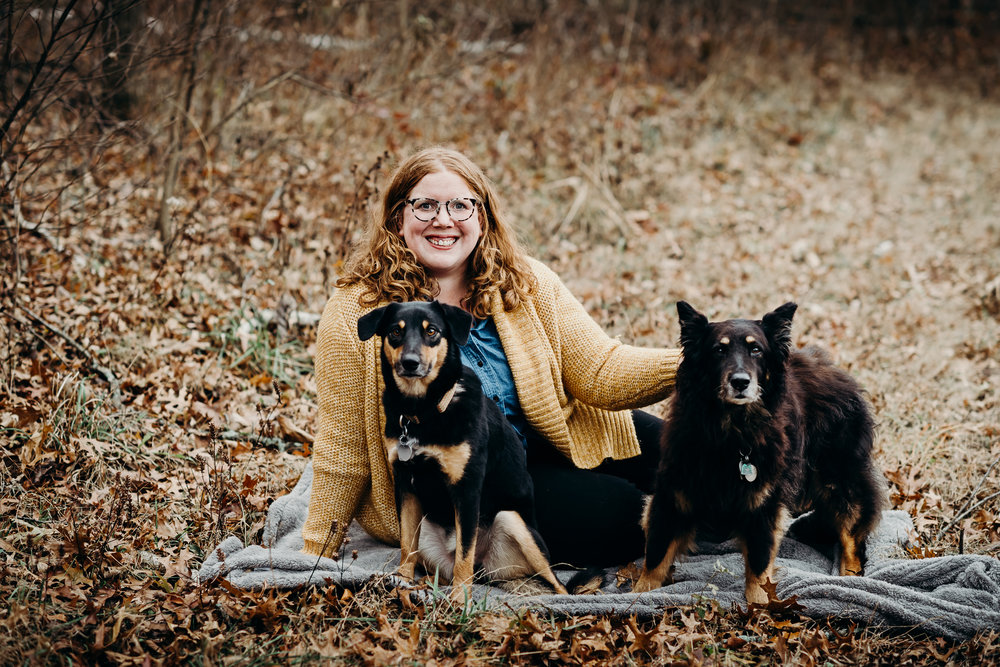 Woman sits on a blanket in the woods with her two black dogs.