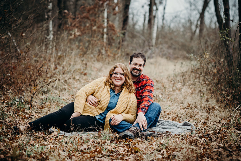 Engaged couple smiling happily as they sit and snuggle on a blanket in the woods.