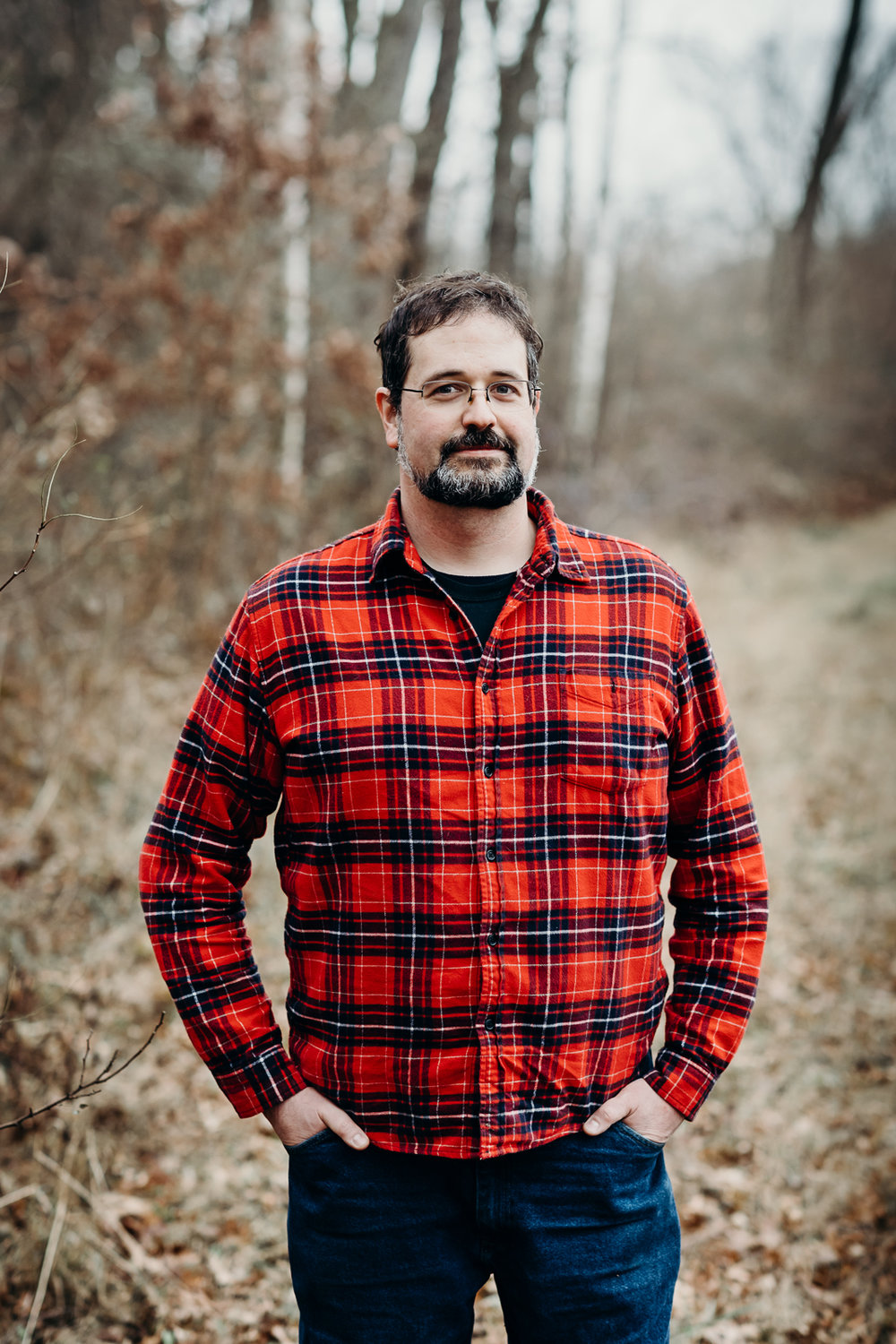 Man in a red flannel with hands in pants pockets.