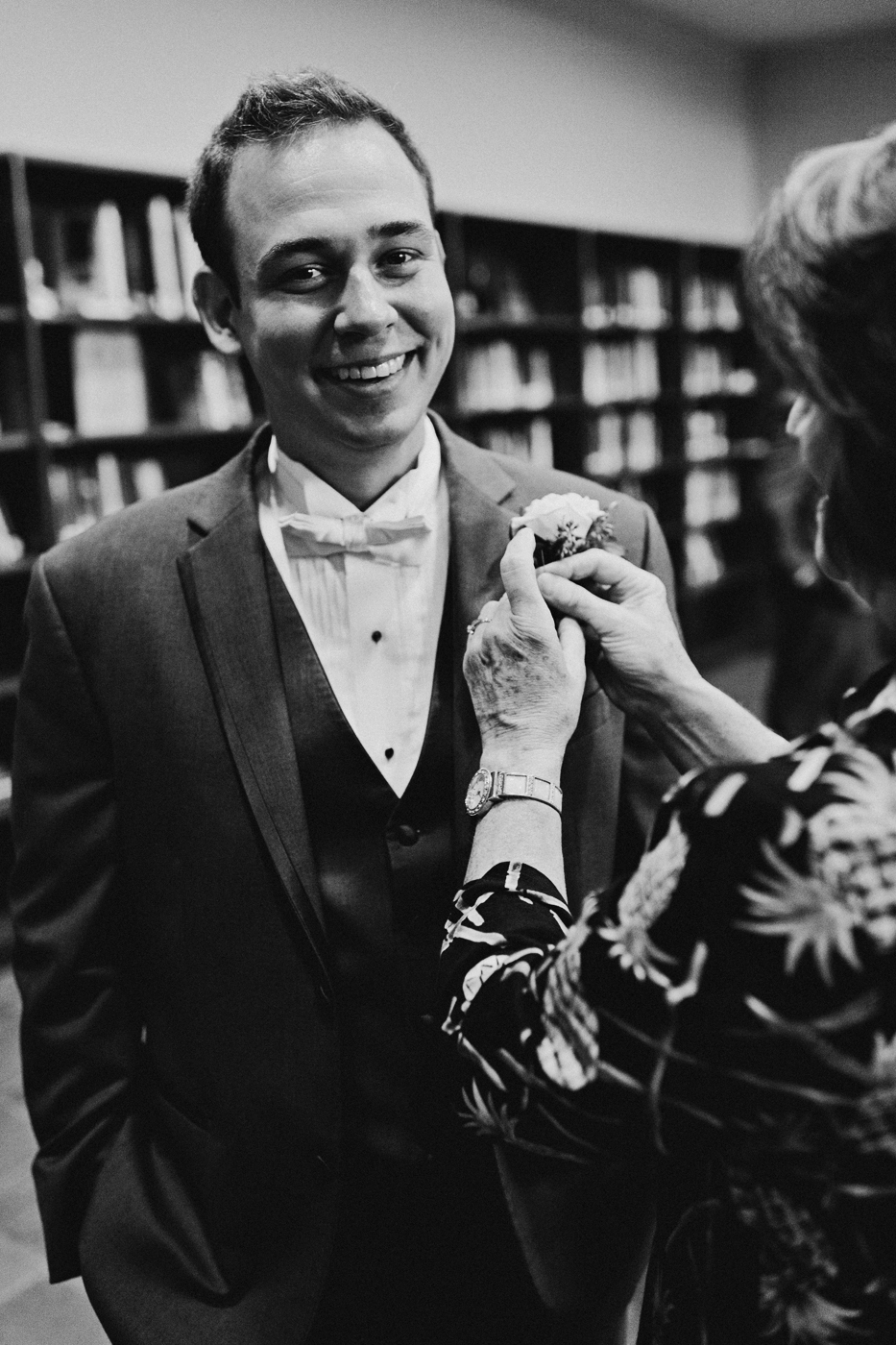 Groom gets boutonniere pinned on