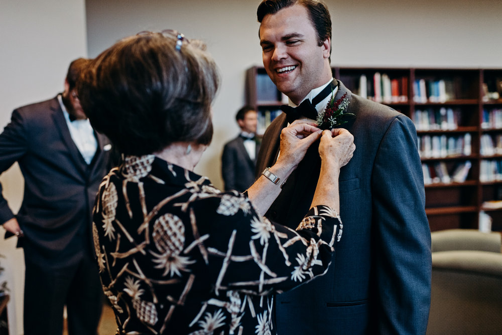 Groomsman gets boutonniere pinned on