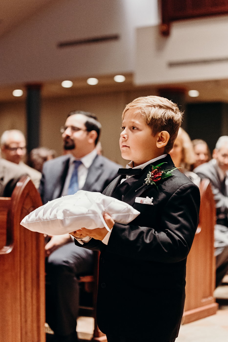 Ring bearer serious as he walks down the aisle
