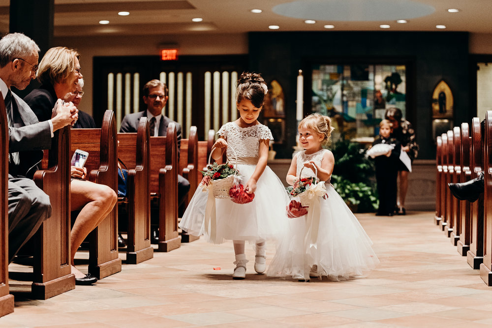 Flower girls drop rose petals walking down the aisle