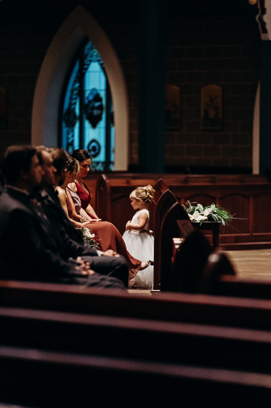 Flower girl standing in the pew during the wedding ceremony