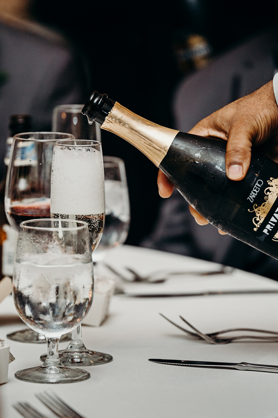 Waiter pours champagne for wedding toast