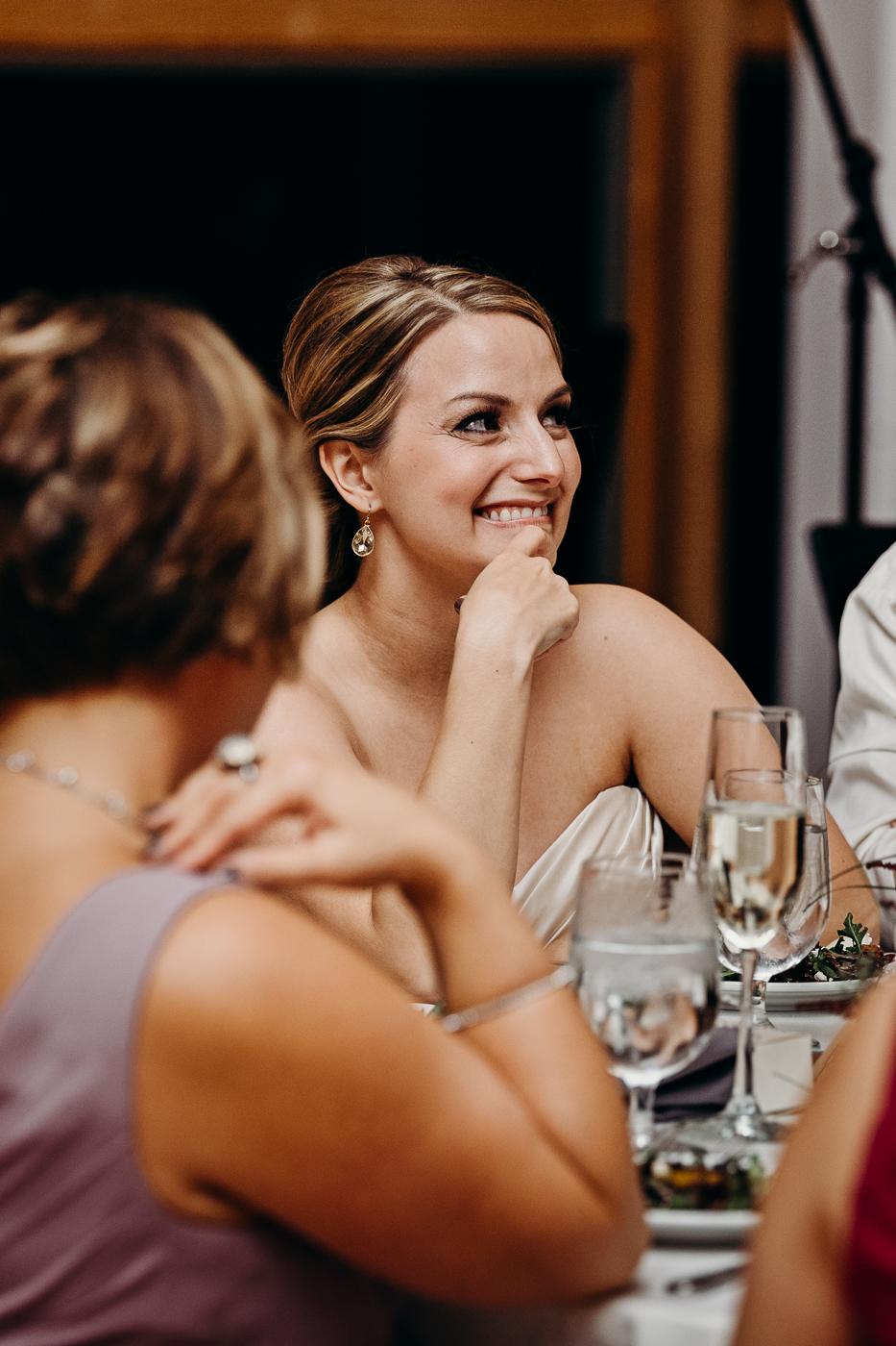 Bride smiles during maid of honor's speech