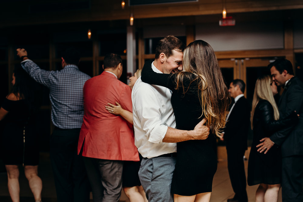 Couple leans into each other's foreheads while dancing at a wedding reception