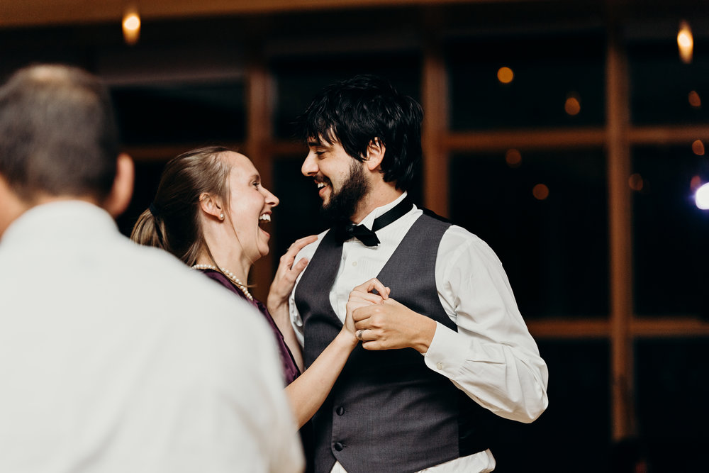 Couple laughs while dancing at wedding reception