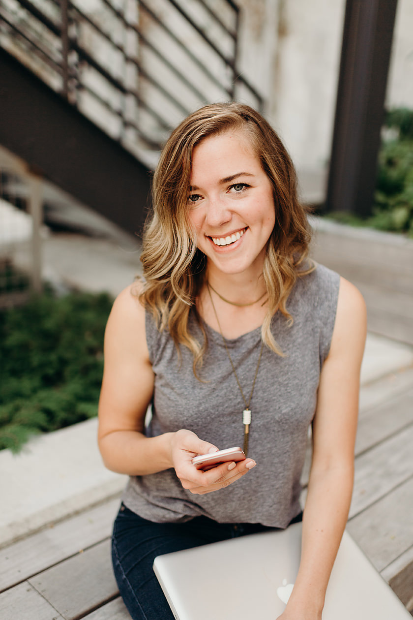 Graphic designer smiling with phone in hand