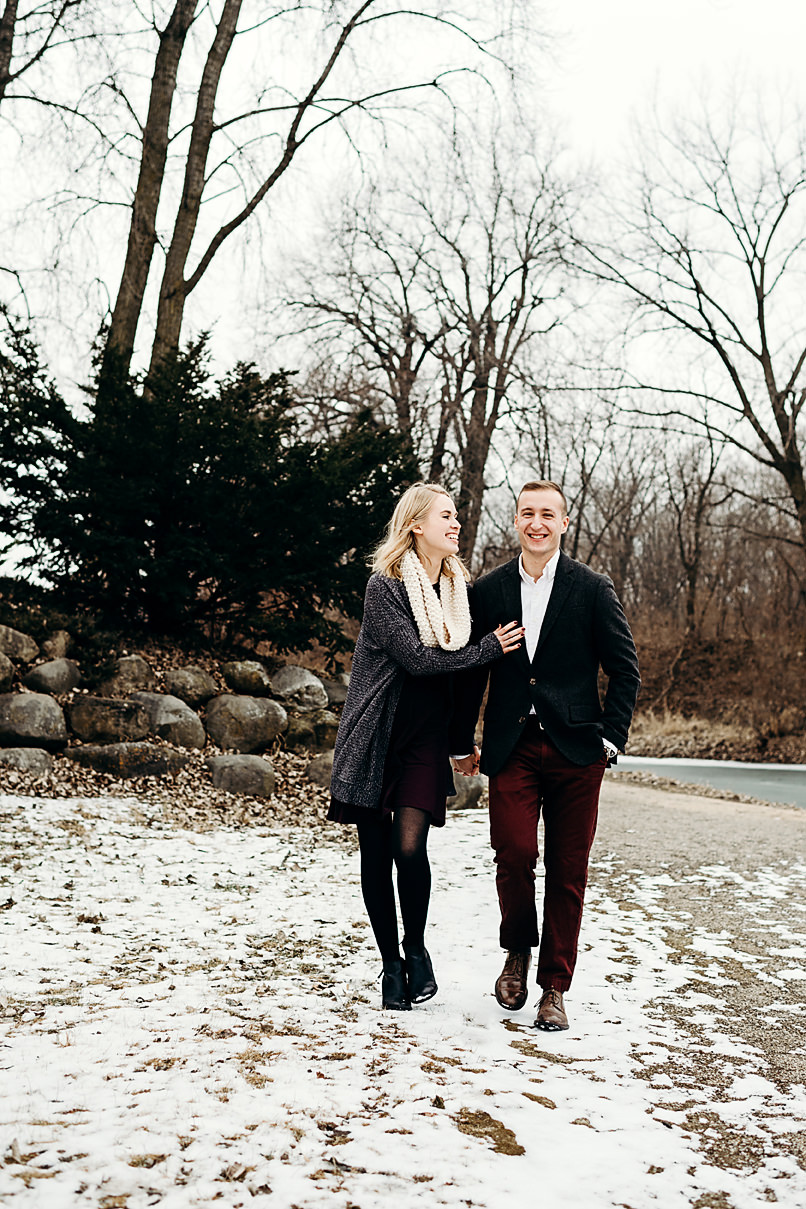 Engaged couple walks arm in arm laughing
