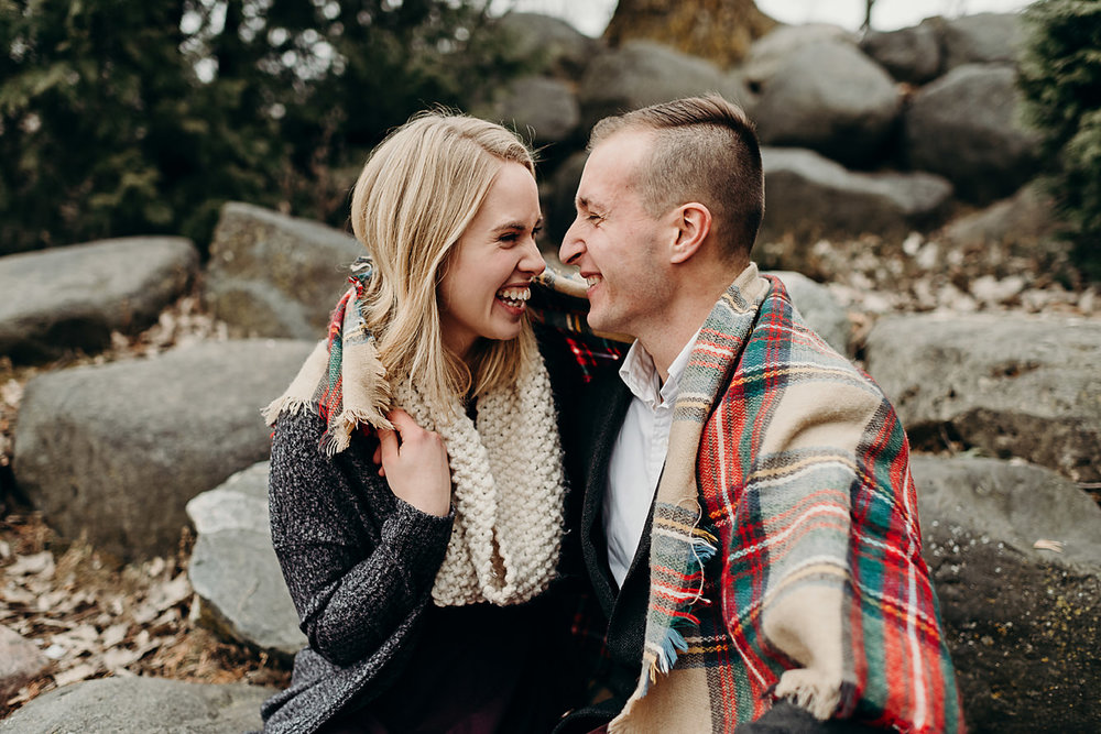 Engaged couple warms up together in a blanket