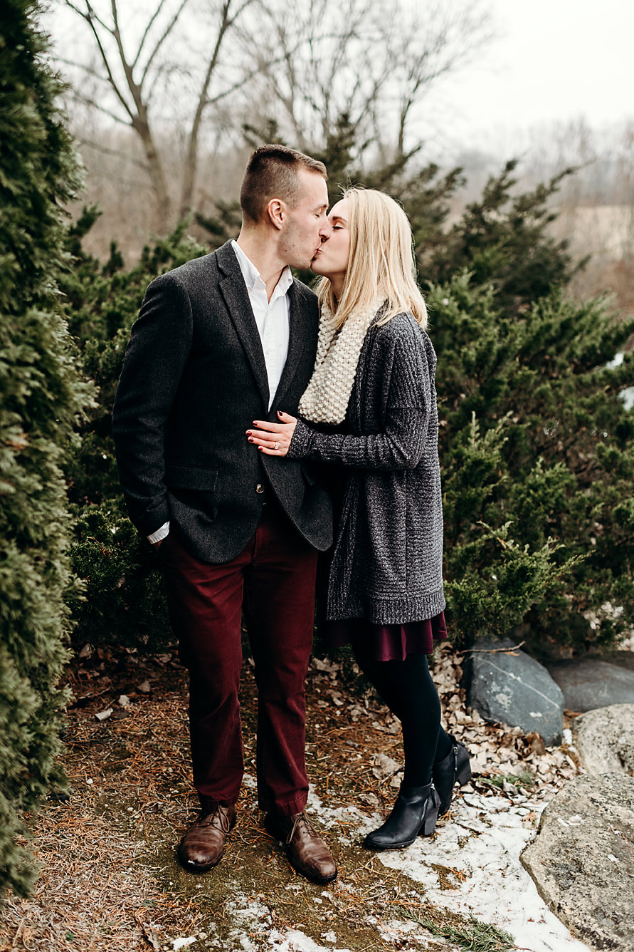 Engaged couple kissing in a park