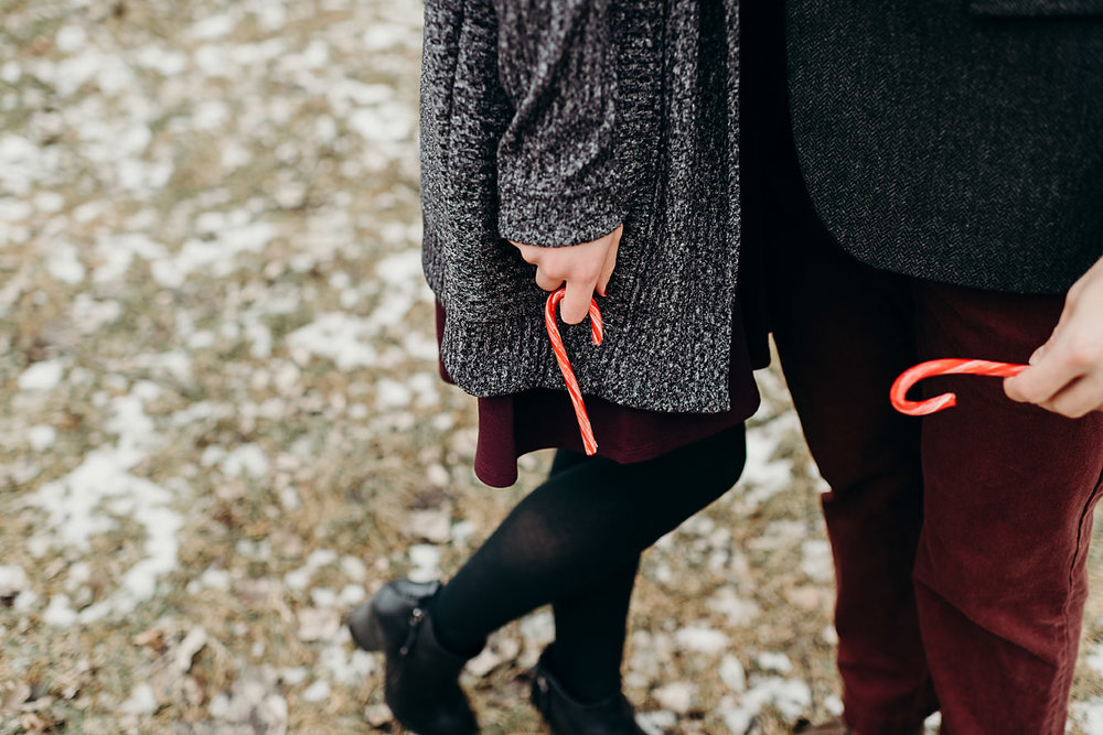 Engaged couple holding candy canes