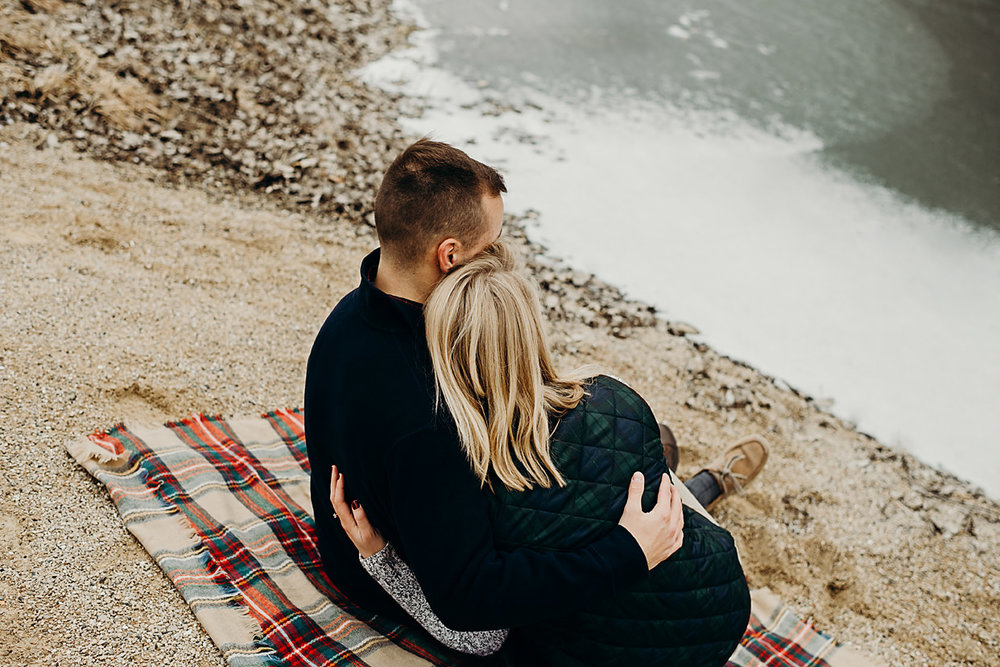 Engaged couple sit and snuggle outside on a blanket