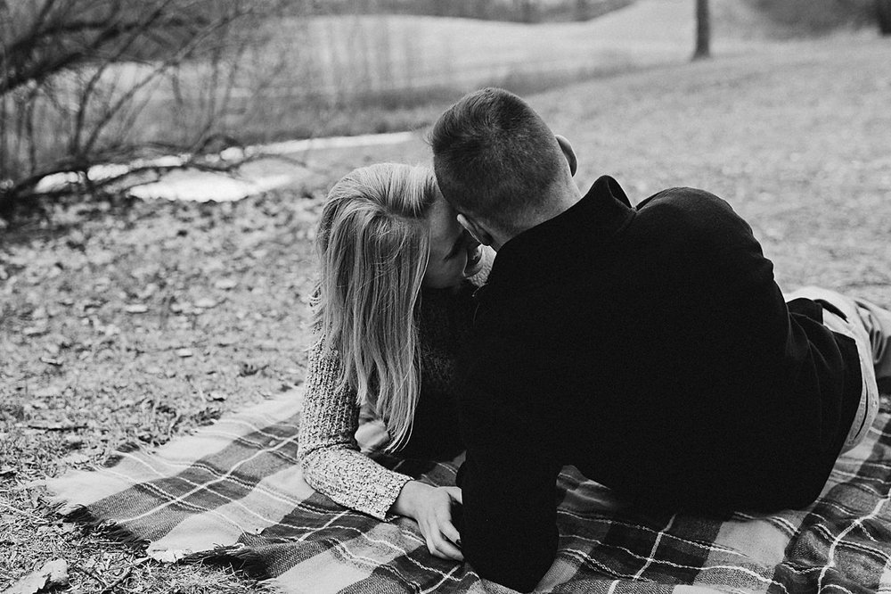 Engaged couple together on a blanket