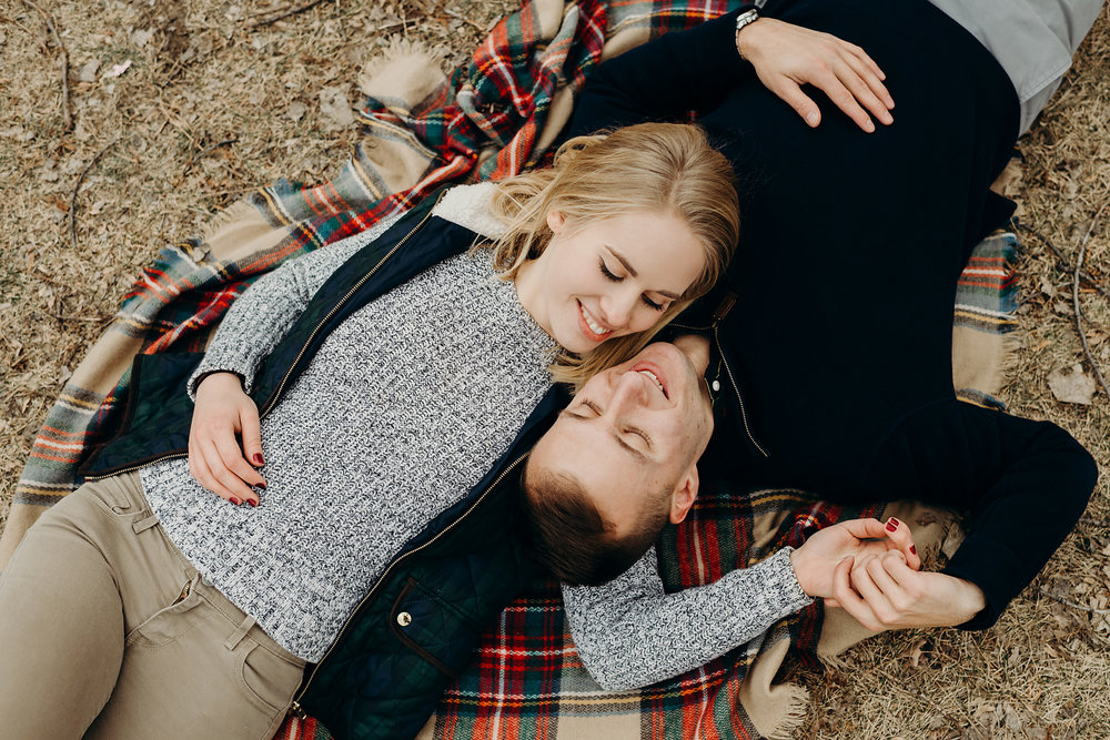 Engaged couple lays down on a blanket outside
