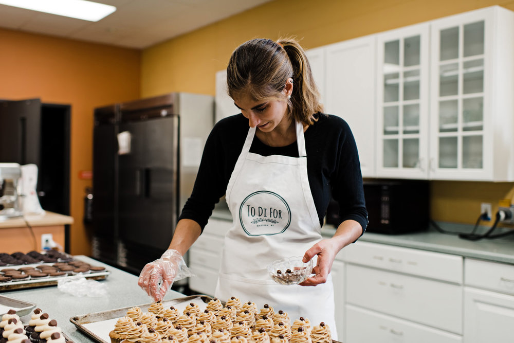 Owner of To Di For Baking topping cupcakes with chocolate covered coffee beans