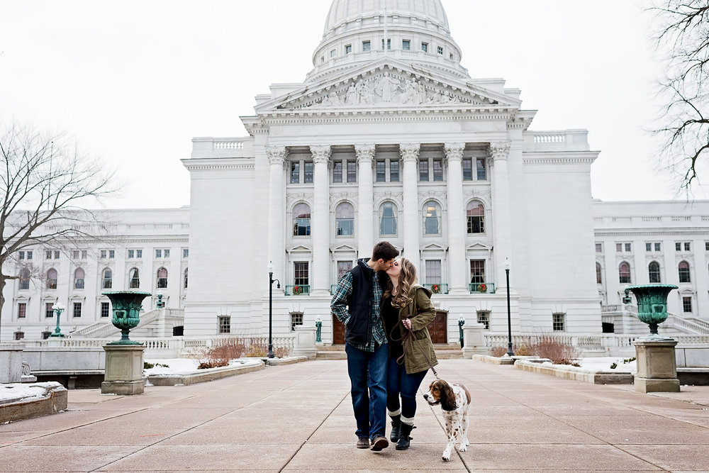 Couple walking with dog in front of Wisconsin state capitol