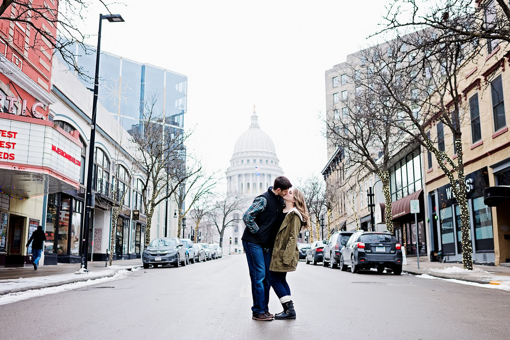Couple kissing with Wisconsin state capitol in the background