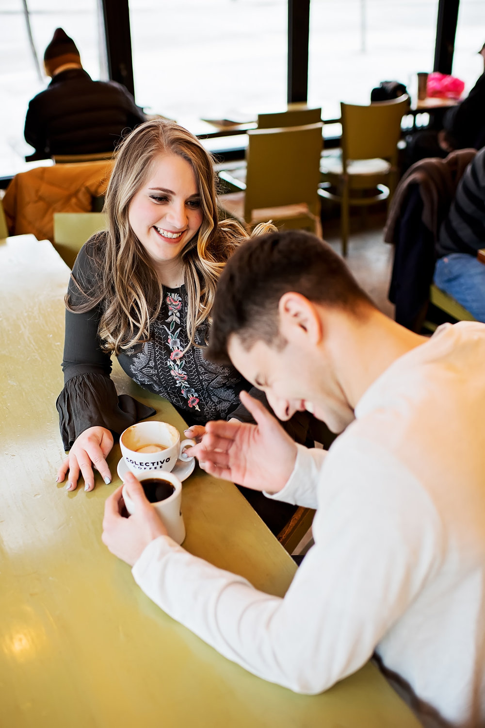 Man laughing with fiancé at a coffee shop