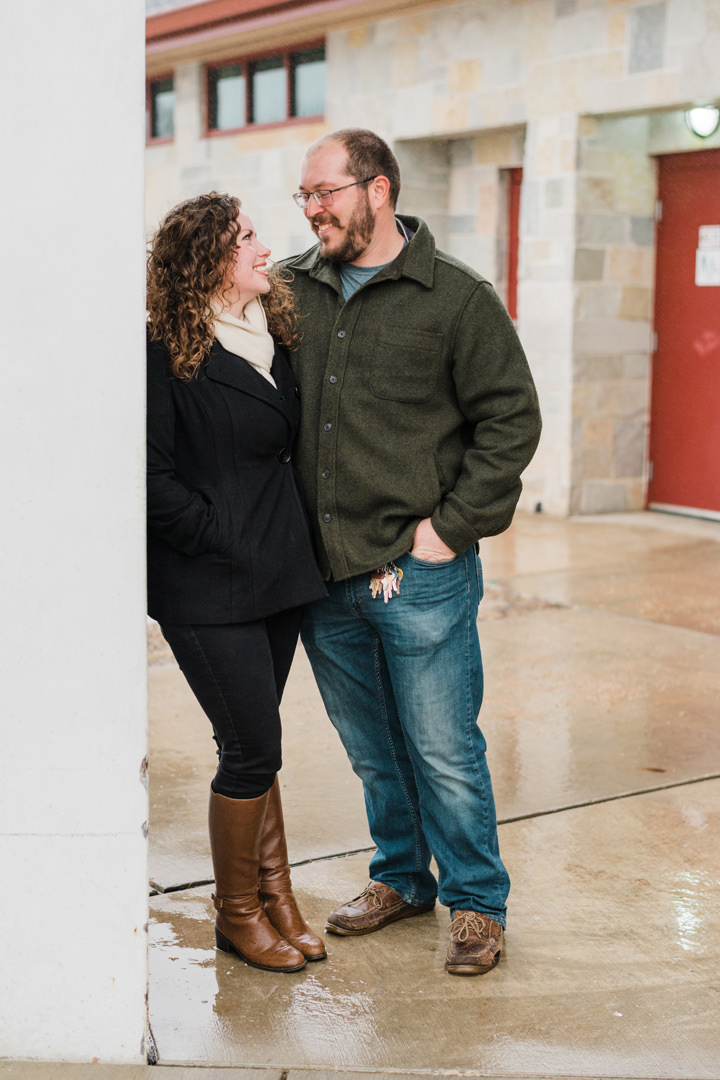 Engaged couple leaning against a pillar