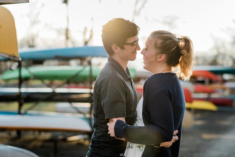 Engaged couple laughing by colorful canoes