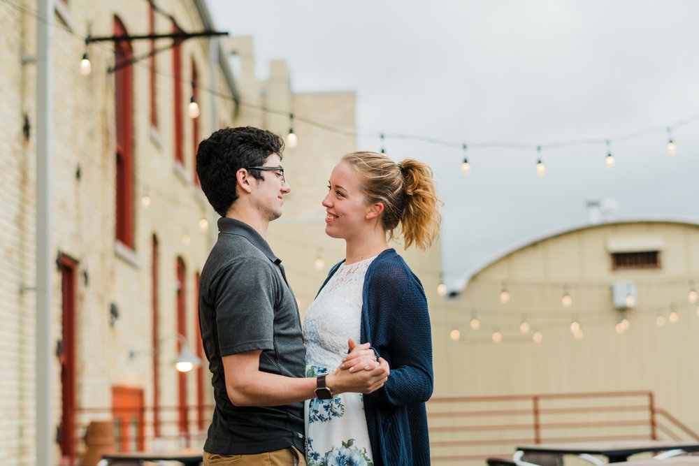 Engaged couple dancing by string lights