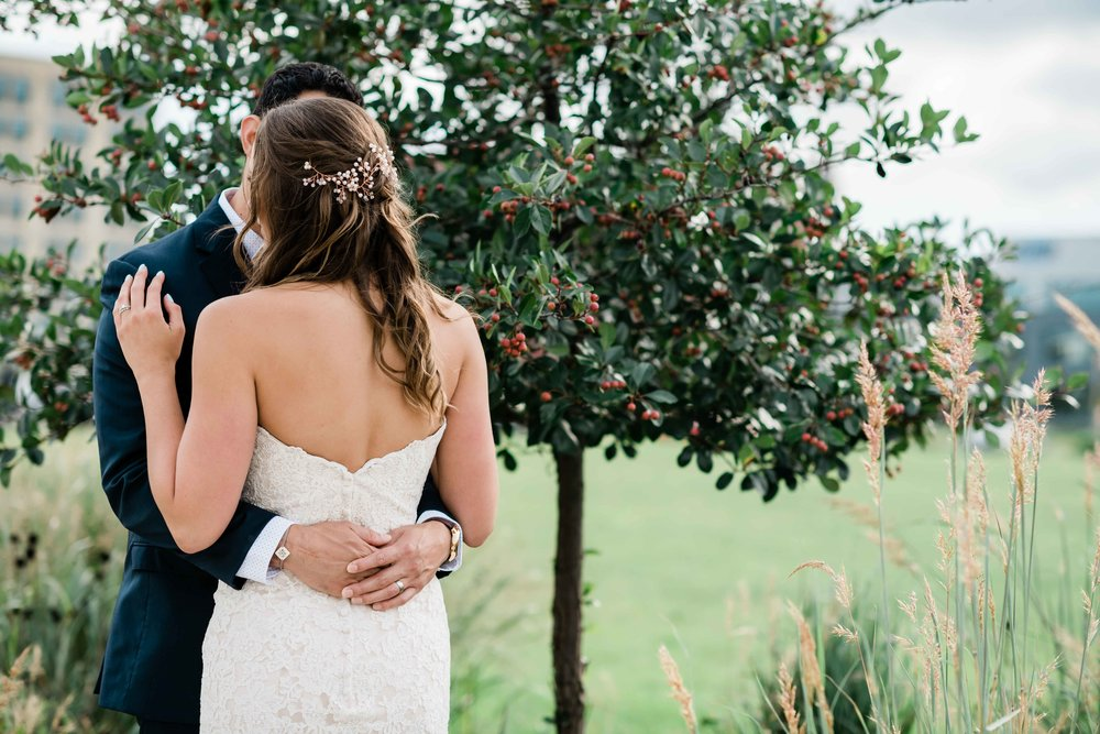 Newlyweds embracing near a crabapple tree.
