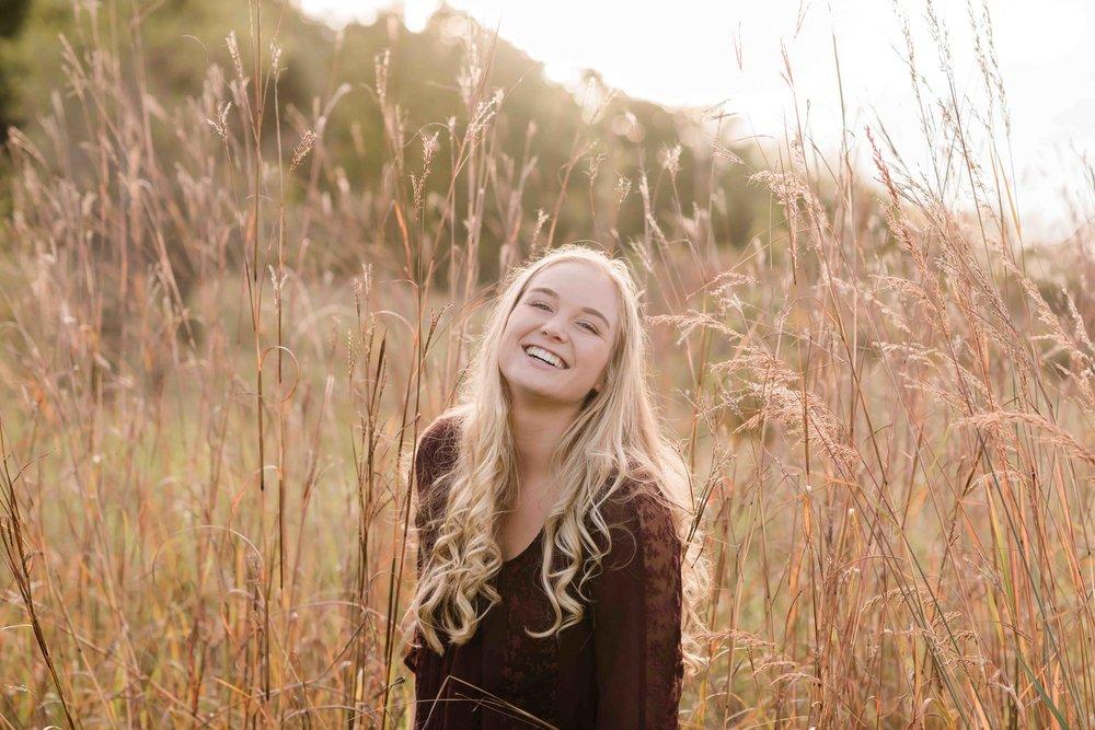 High school senior smiling in a field
