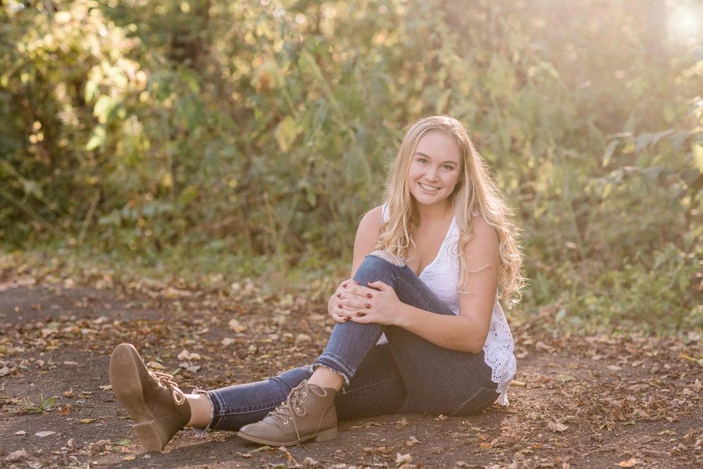 High school senior sitting on a path
