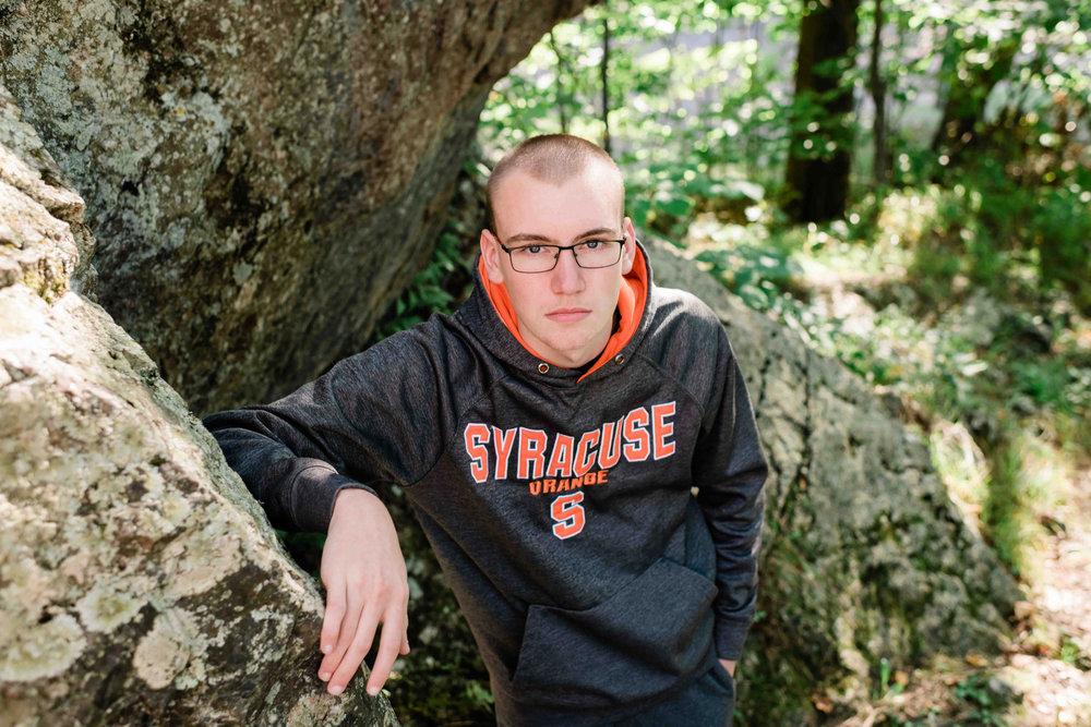 High school senior leaning against a big rock
