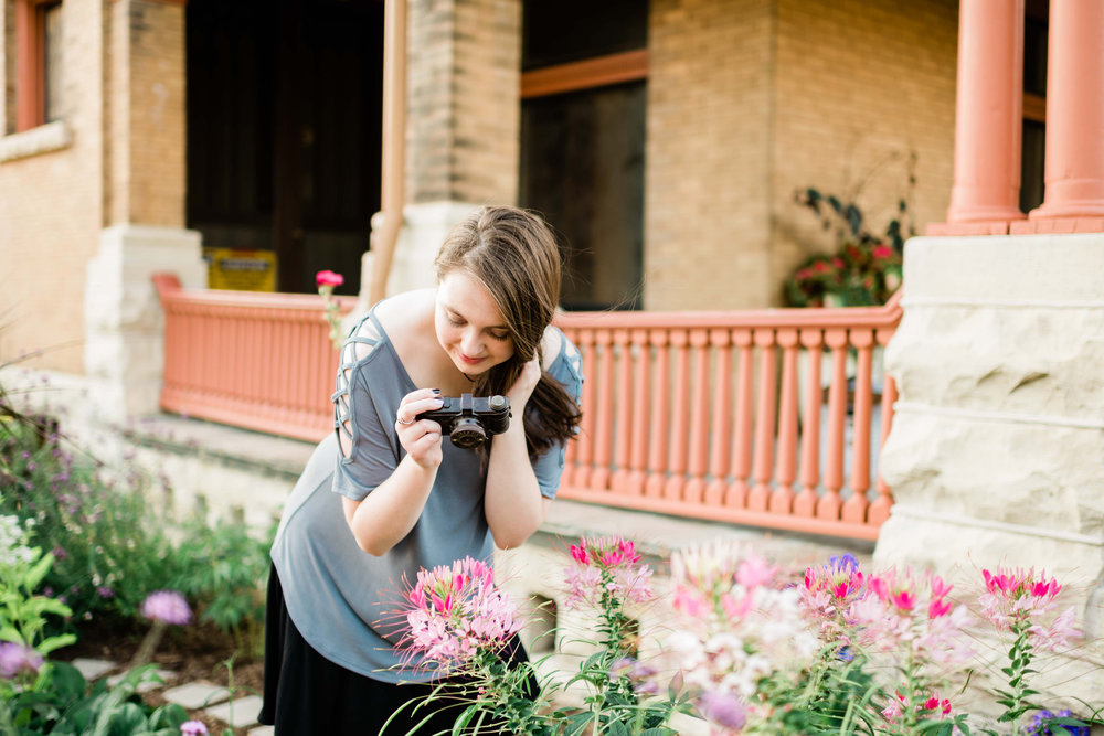 High school senior taking photos of flowers