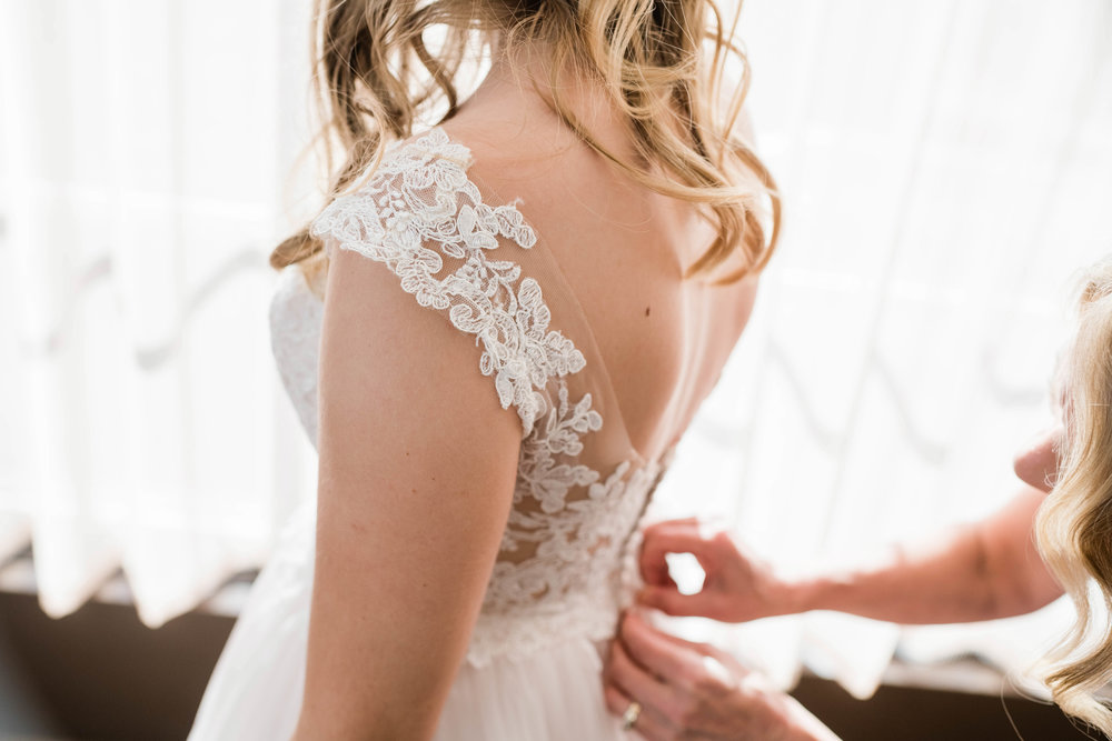 Mother fastening up her daughter's bridal gown