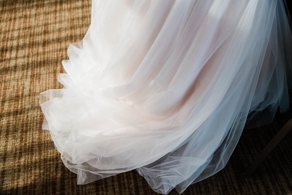 Sunlight shines on the bottom of a wedding dress