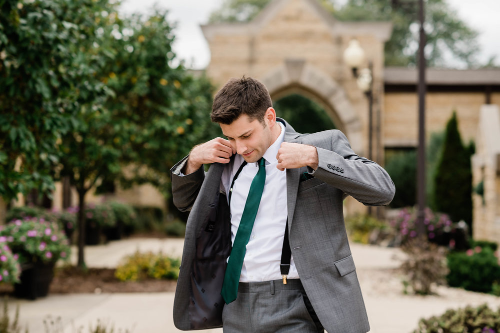 Groom putting on his suit jacket