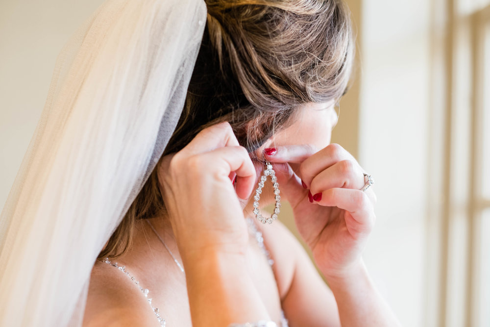 Bride putting on an earring