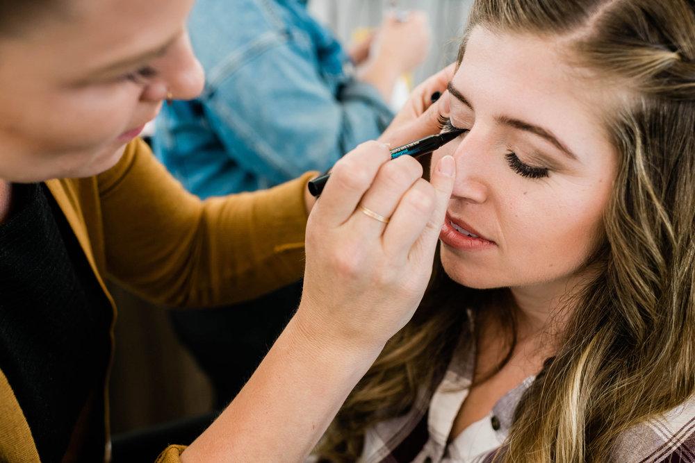 Makeup artist applying bride's eye makeup