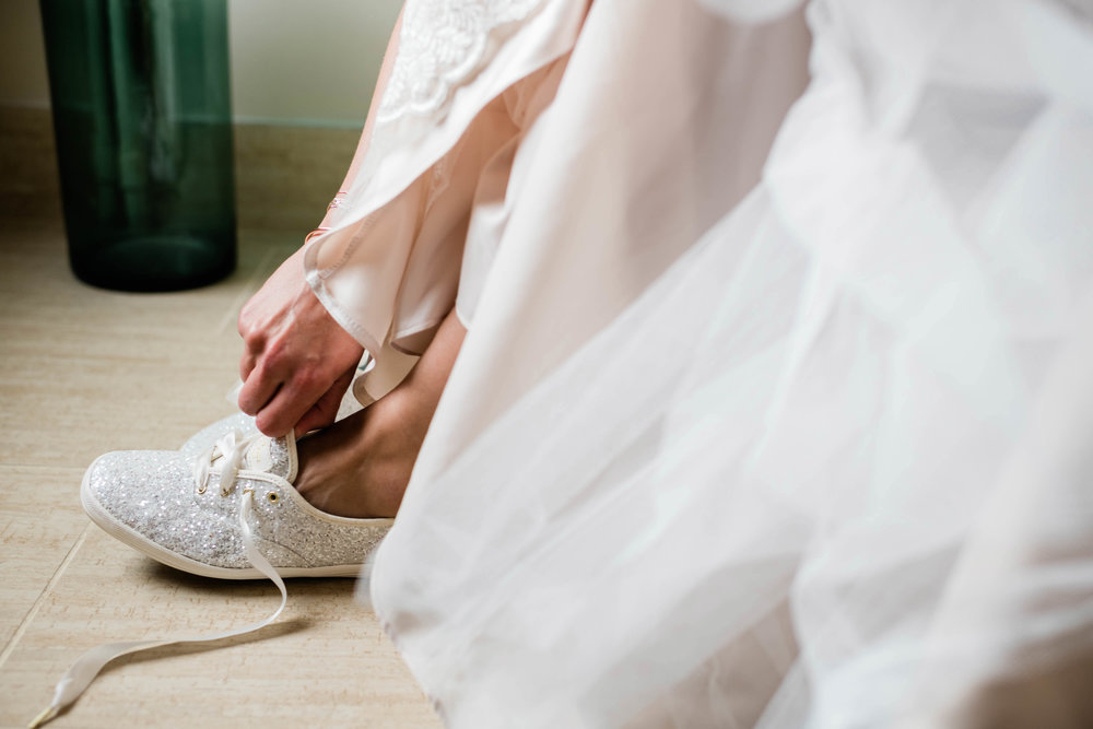 Bride putting on her glitter Keds shoes