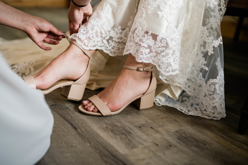 Bridesmaid fastens bride's shoe strap