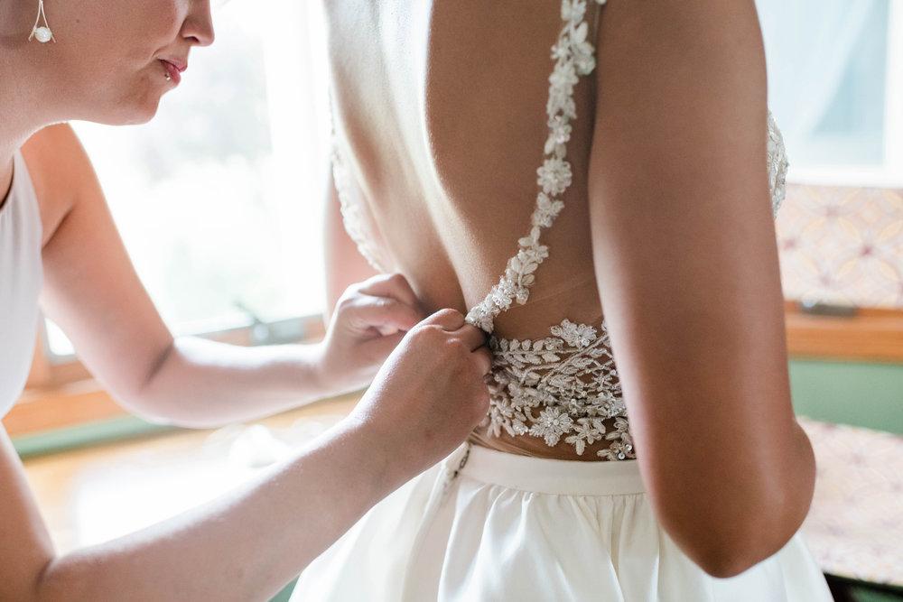 Bridesmaid buttons up bride's wedding dress