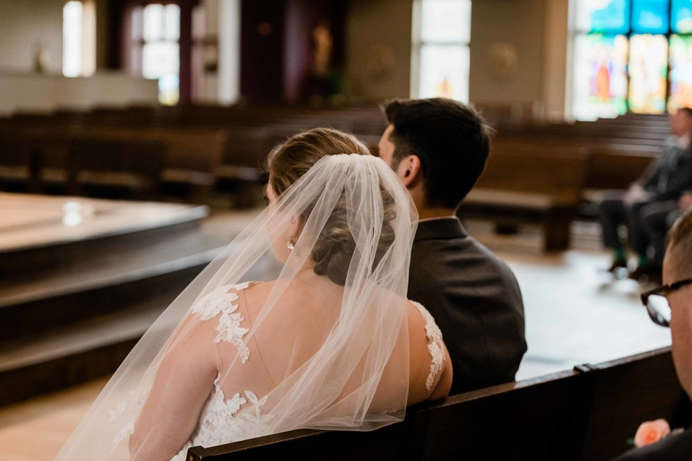 Bride and groom sit and listen to the priest at their wedding
