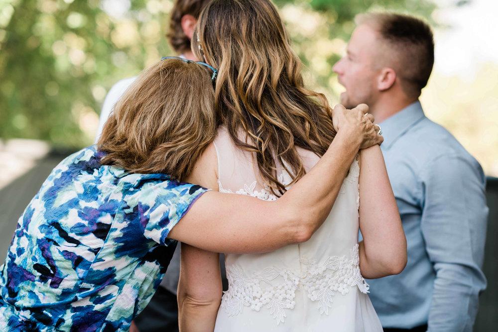 Wedding guest wraps her arm around the bride