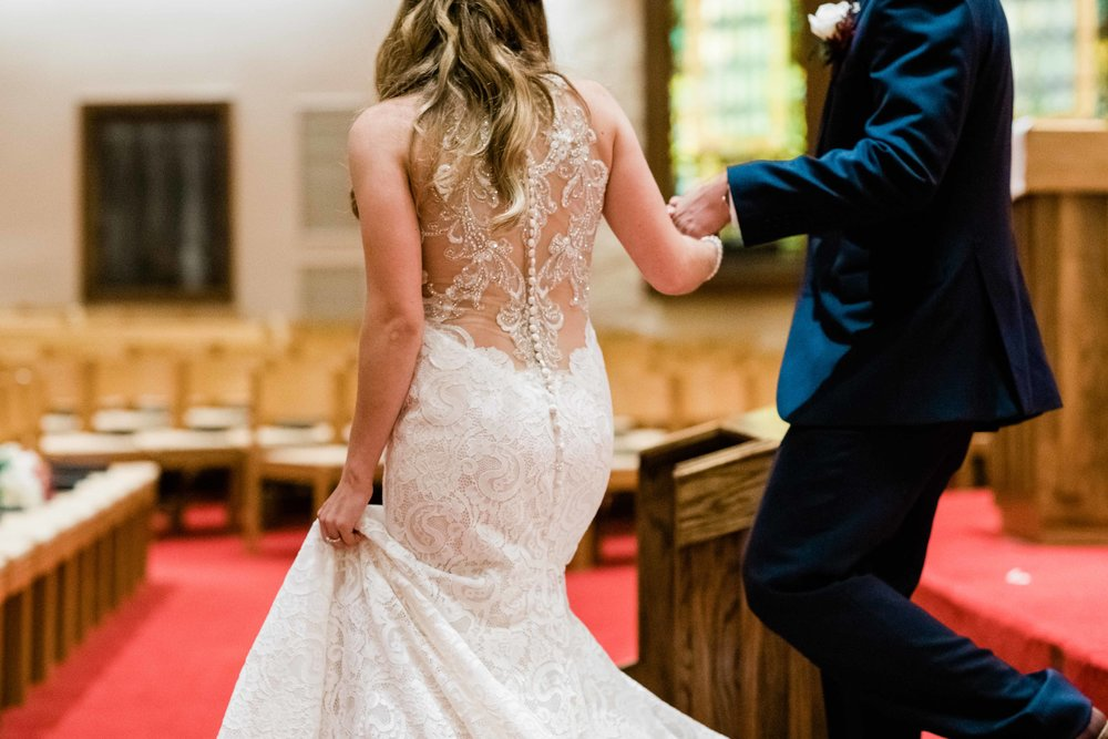 Groom holds bride's hand during wedding ceremony