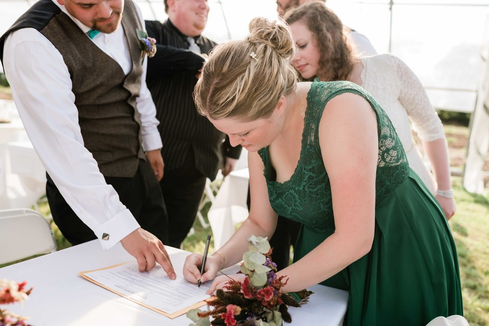 Bridesmaid signing as a witness on the marriage license