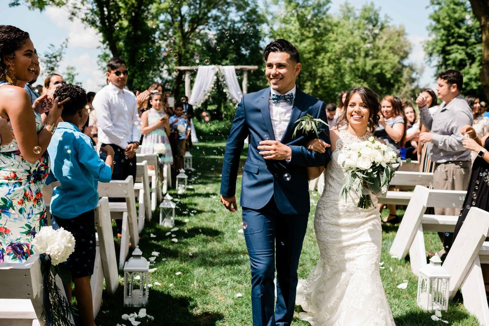 Bride and groom walk through bubbles after their ceremony