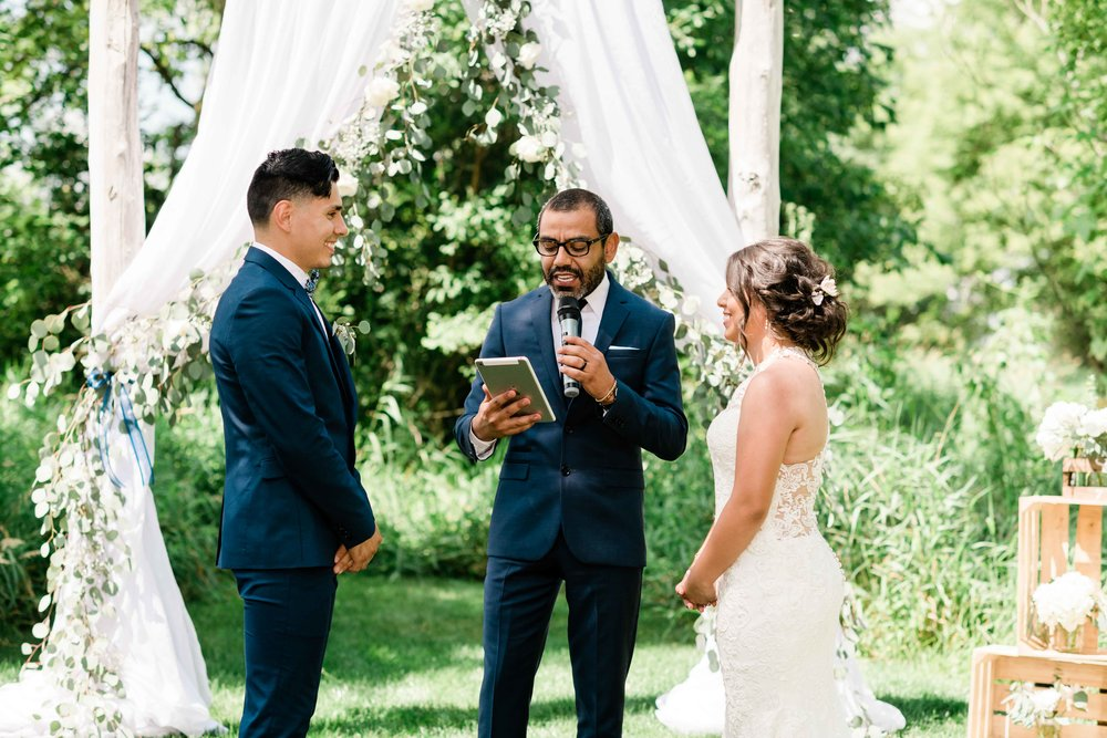 Bride and groom with the officiant at the altar